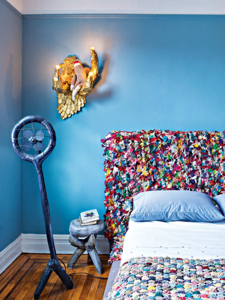 The master bedroom features a super colorful headboard and a matching bedspread, crazy furniture and lamps designed by the couple