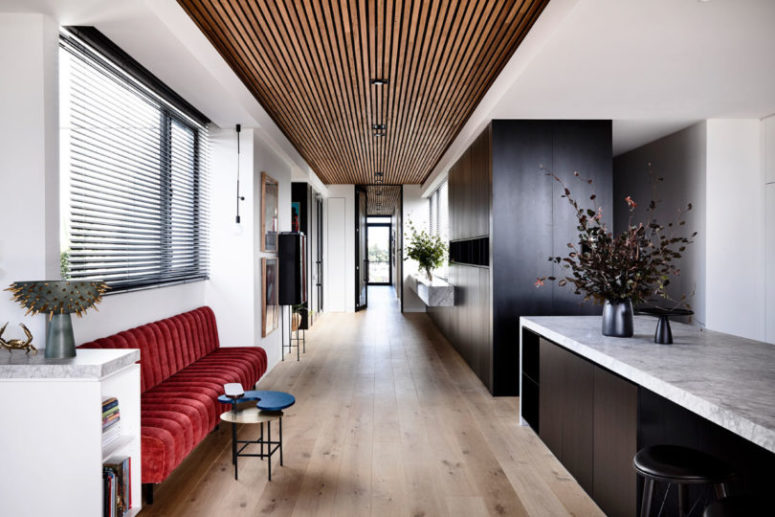There's a large dark storage unit in the kitchen and a red upholstered bench as a bold touch