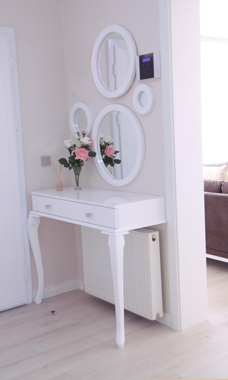 a chic vintage-inspired makeup nook done with a half table and several mirrors