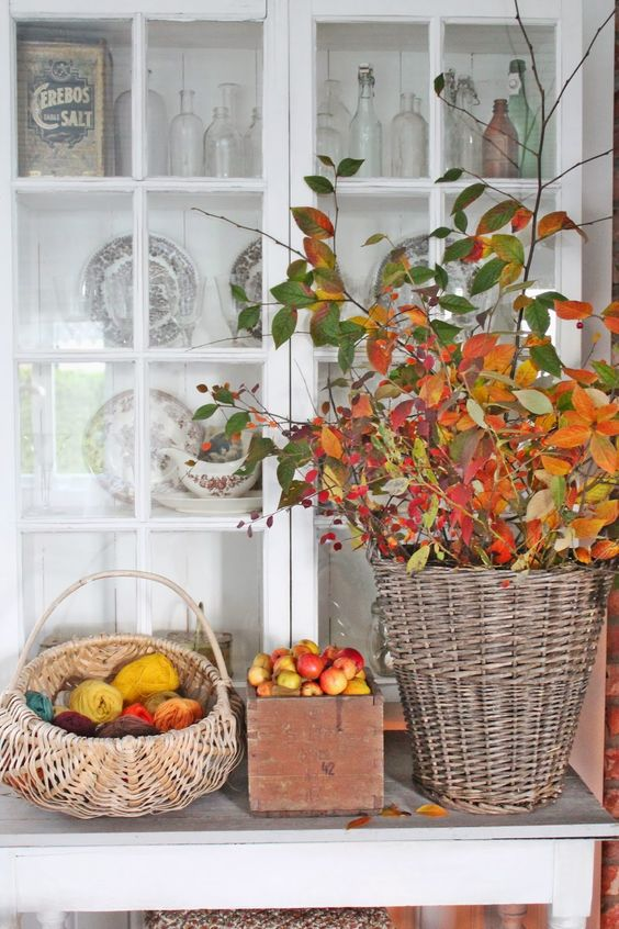 a fall display of baskets with colorful yarn and fall leaves and a crate with fresh apples