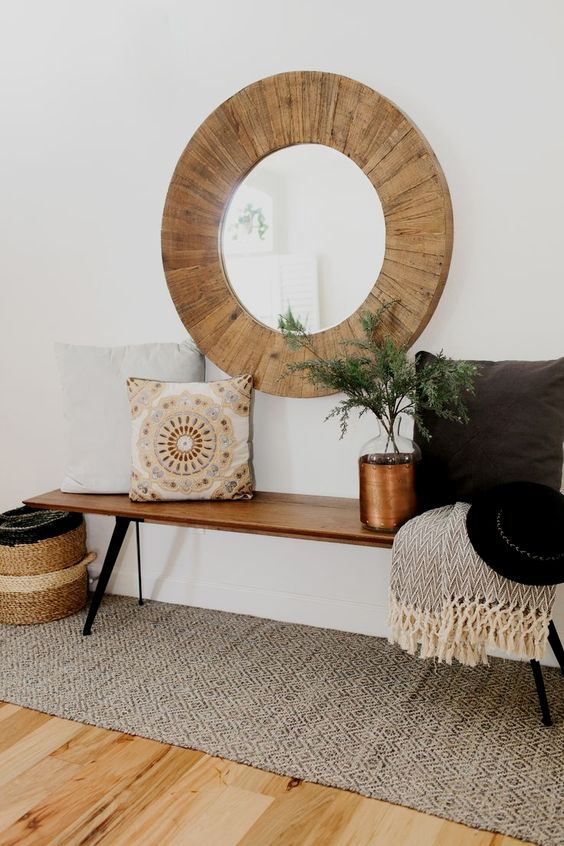 a large round mirror clad with wood is ideal for a rustic or boho chic space, it will add coziness