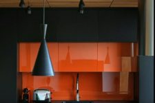 03 a minimalist kitchen in black and orange, with a glass backsplash and cool pendant lamps in black