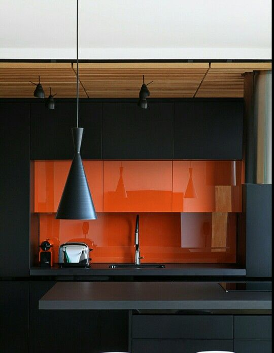 a minimalist kitchen in black and orange, with a glass backsplash and cool pendant lamps in black