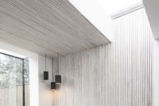 03 a minimalist space is enlivened and made more interesting with a whitewashed paneled wall and ceiling