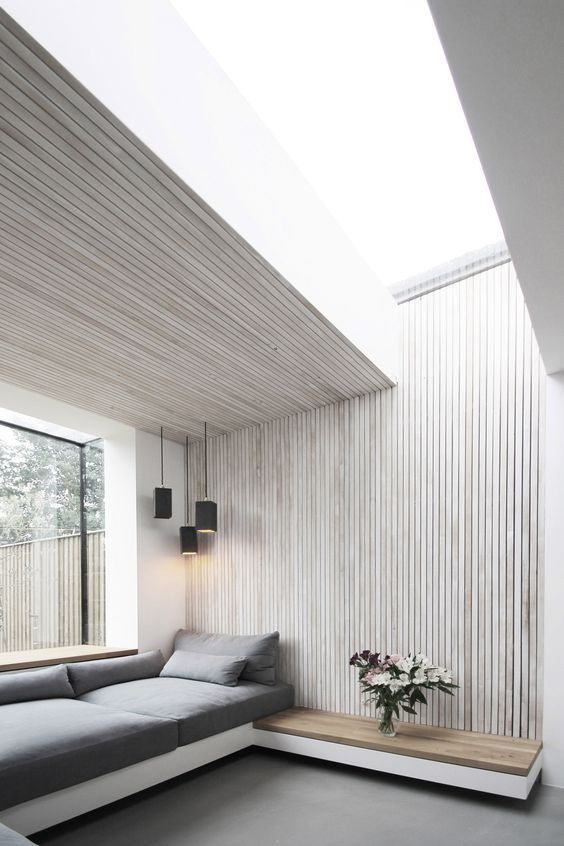 a minimalist space is enlivened and made more interesting with a whitewashed paneled wall and ceiling