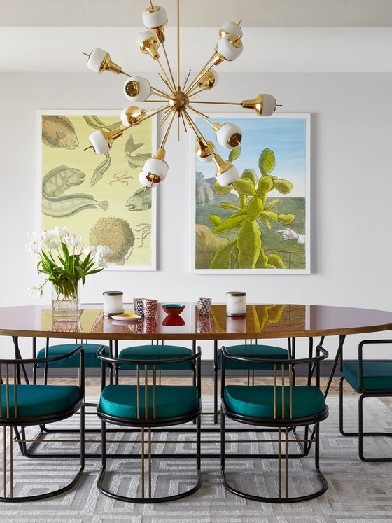 The dining space features gorgeous teal chairs and a duo of mid-century posters