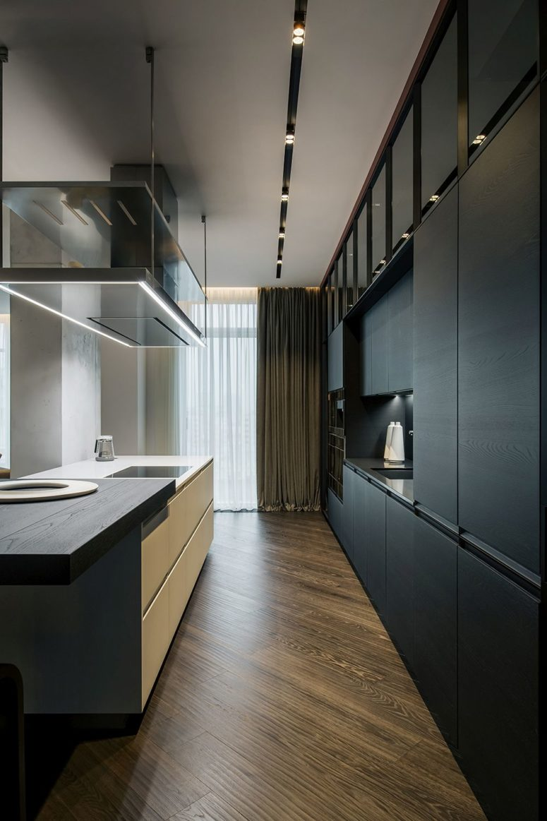 The kitchen is done with sleek black plywood cabinets and a white kitchen island with a plywood countertop