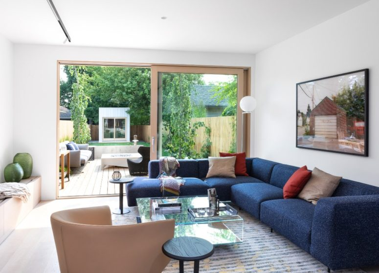 The living room is a united indoor-outdoor space with a bold blue corner sofa, catchy furniture and storage items