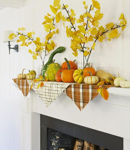 a fall mantel with a lot of pumpkins and gourds and yellow leaves in clear vases