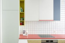 04 a minimalist color block kitchen with coral, aqua and blue accents and white tiles with black grout