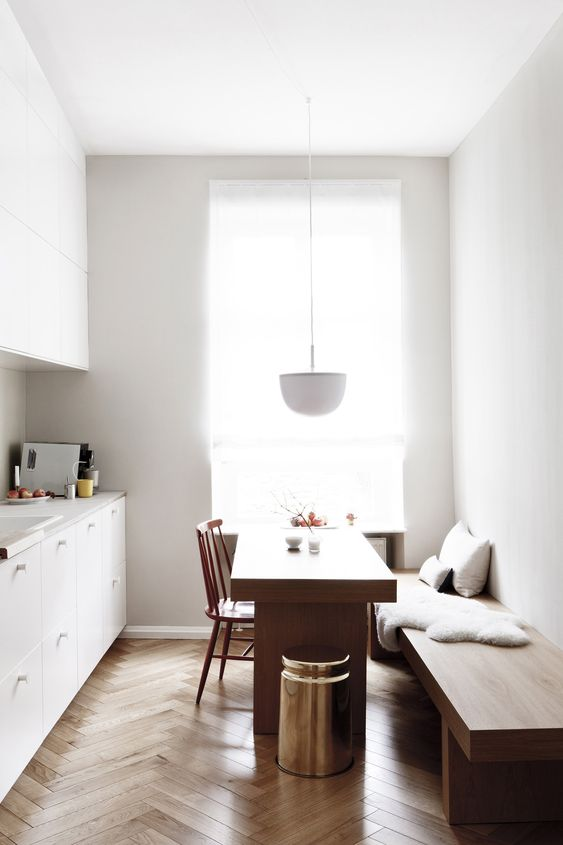 a minimalist space with a comfy bench and a dining table, which can be used as a kitchen island, too