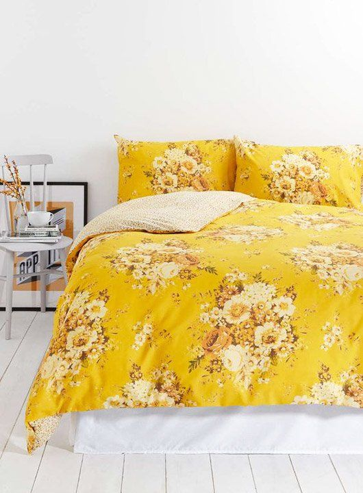 a neutral space with bold yellow floral print bedding for a romantic touch