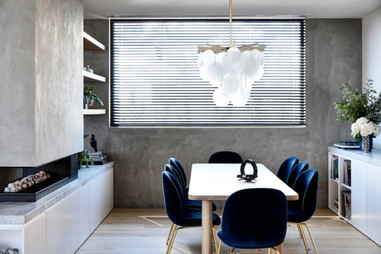 The dining space features contrasting navy chairs of velvet with brass legs