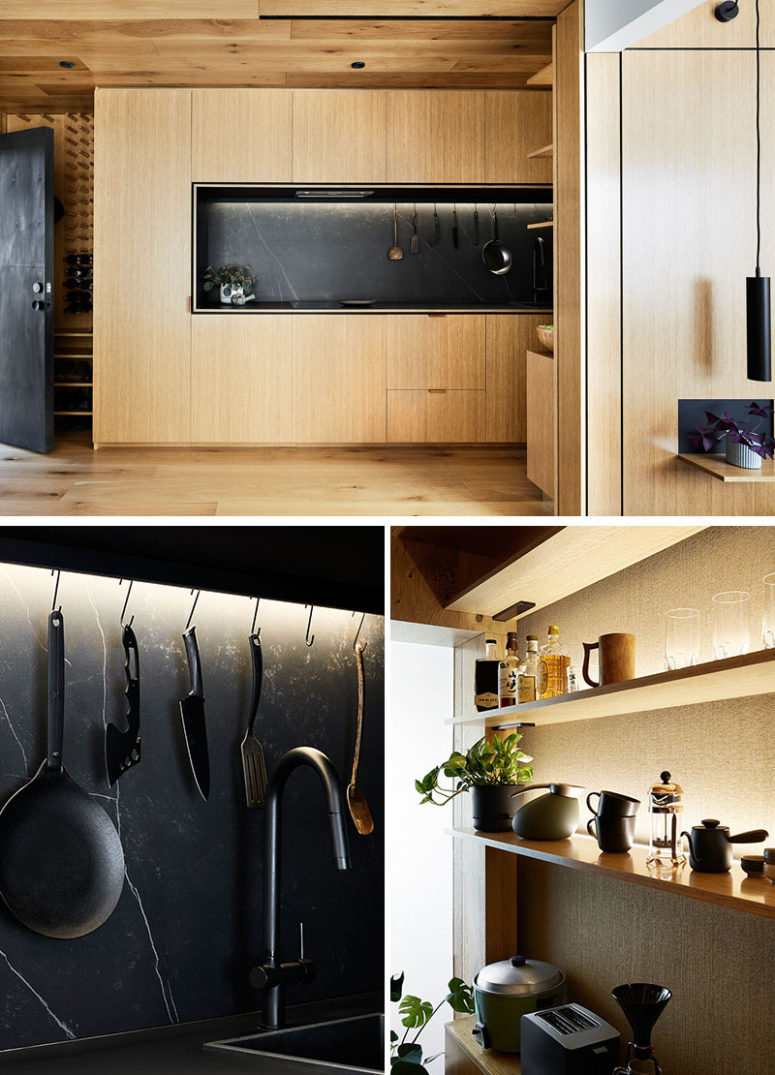 The kitchen is a light-colored wood unit with black marble for a contrast
