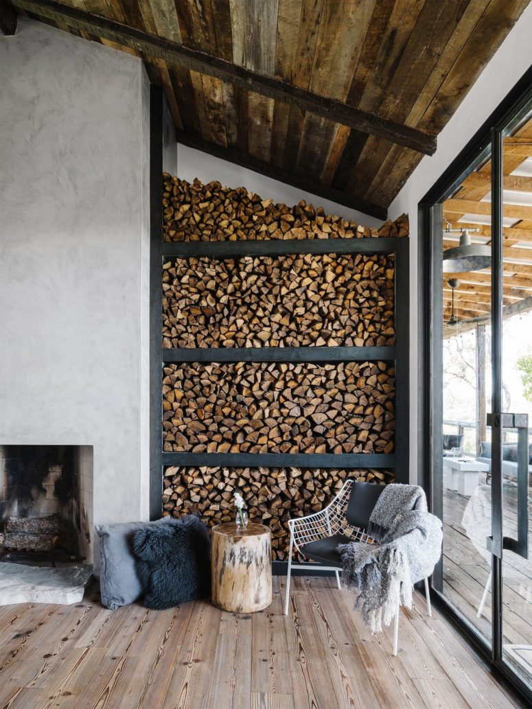 The living room features a concrete clad fireplace, a sitting zone by the window and a firewood storage