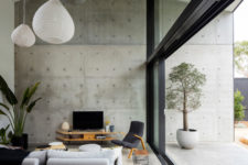 05 The living space is done in grey shades with black, with light-colored plywood