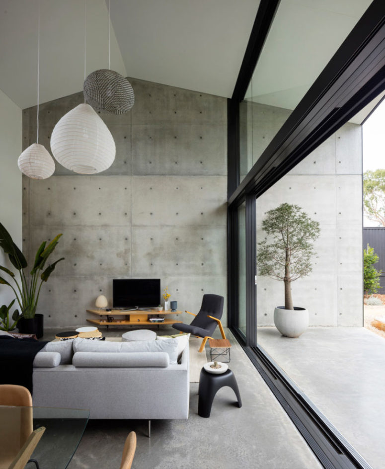 The living space is done in grey shades with black, with light-colored plywood