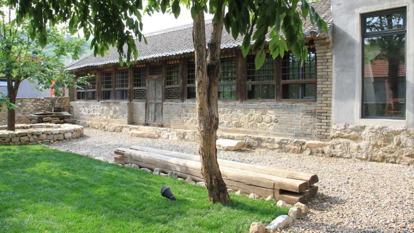 The outdoor spaces are styled with gravel and lawns, there's stone cladding and benches made of logs