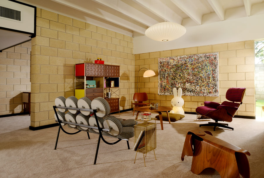 The sitting space is done with bold furniture, wooden touches and a colorful abstract artwork