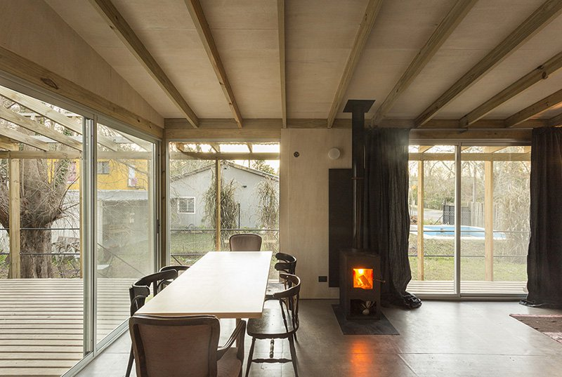 The spaces are done with wooden beams on the ceiling and there are a lot of windows and sliding doors that bring natural light inside