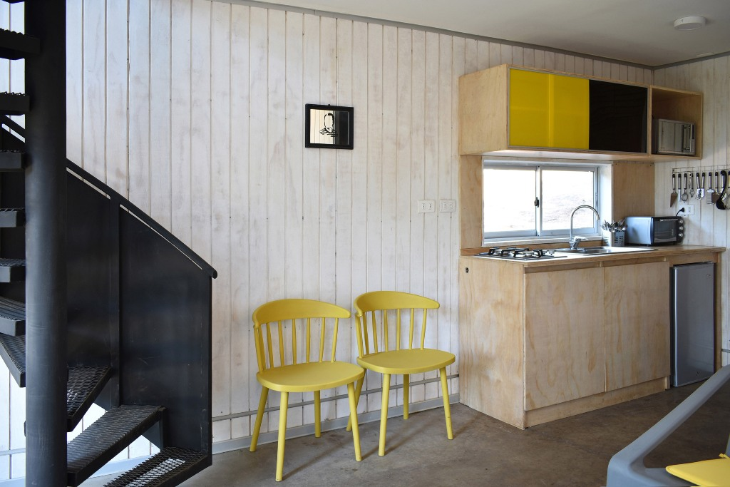There's a kitchen clad with plywood and done with colorful skee panels, and here you can see a staircase leading upstairs
