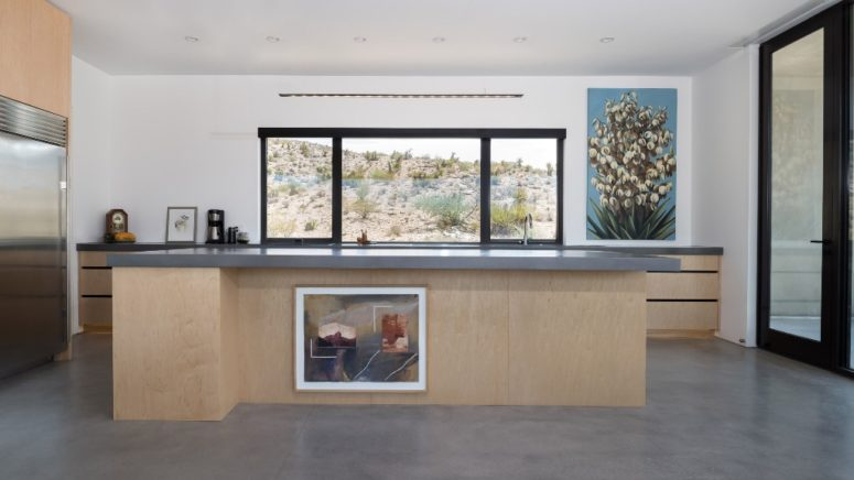 There's a large kitchen with a big kitchen island and cabinets plus desert views