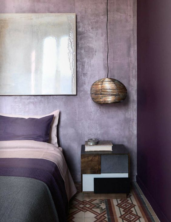 a bold color blocked bedroom with a bright purple wall and lavender plaster ones for an enchanting look