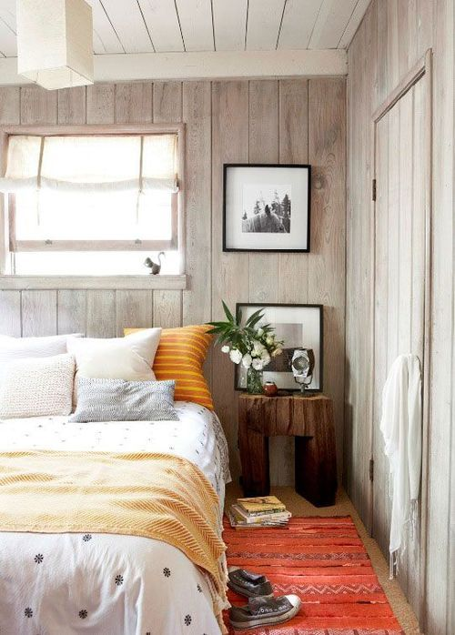 a cozy bedroom with whitewashed wood walls and ceiling spruced up with colorful textiles