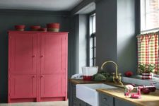05 a grey kitchen with a large pink cabinet for a color block effect is a bold and trendy idea