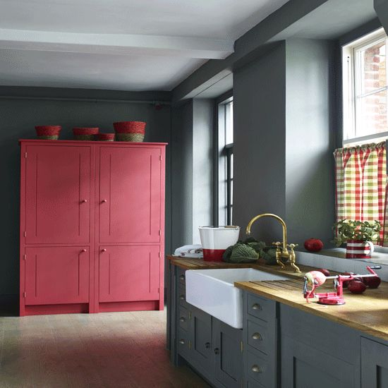 a grey kitchen with a large pink cabinet for a color block effect is a bold and trendy idea
