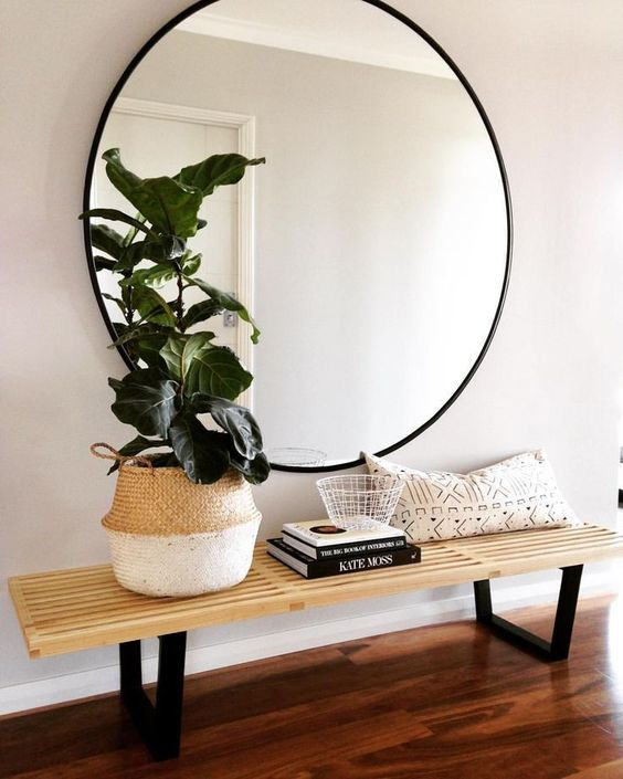 a large round mirror in a black frame and a wooden bench for a simple boho chic space