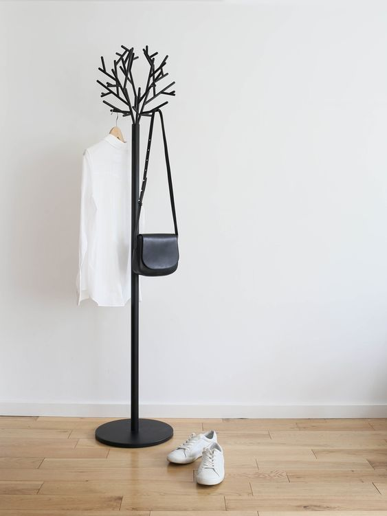a minimalist coat tree imitating a real tree, made of metal with a black finish for easy blending