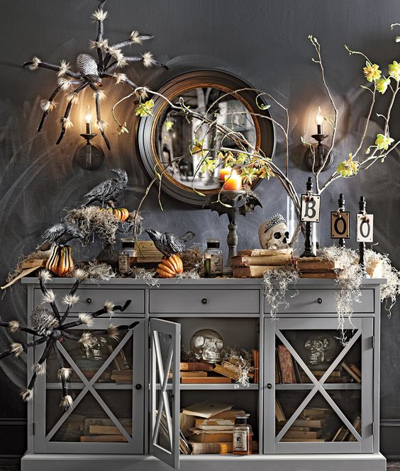 a moody Halloween console with giant spiders, fake pumpkins, skulls and candles