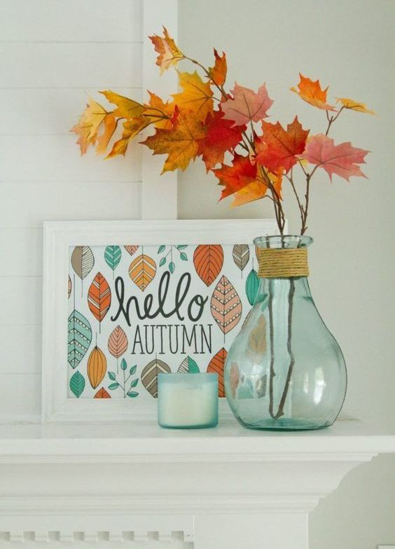 a stylish display with a sign, some fall leaves in a clear vase and a candle in opaque glass