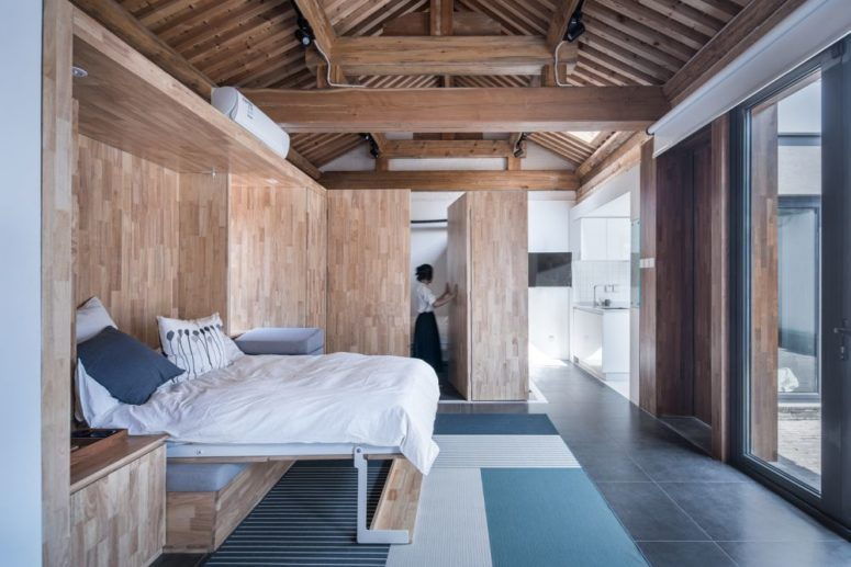 The bedroom is done with light-colored plywood and touches of blue and white for a fresh feeling