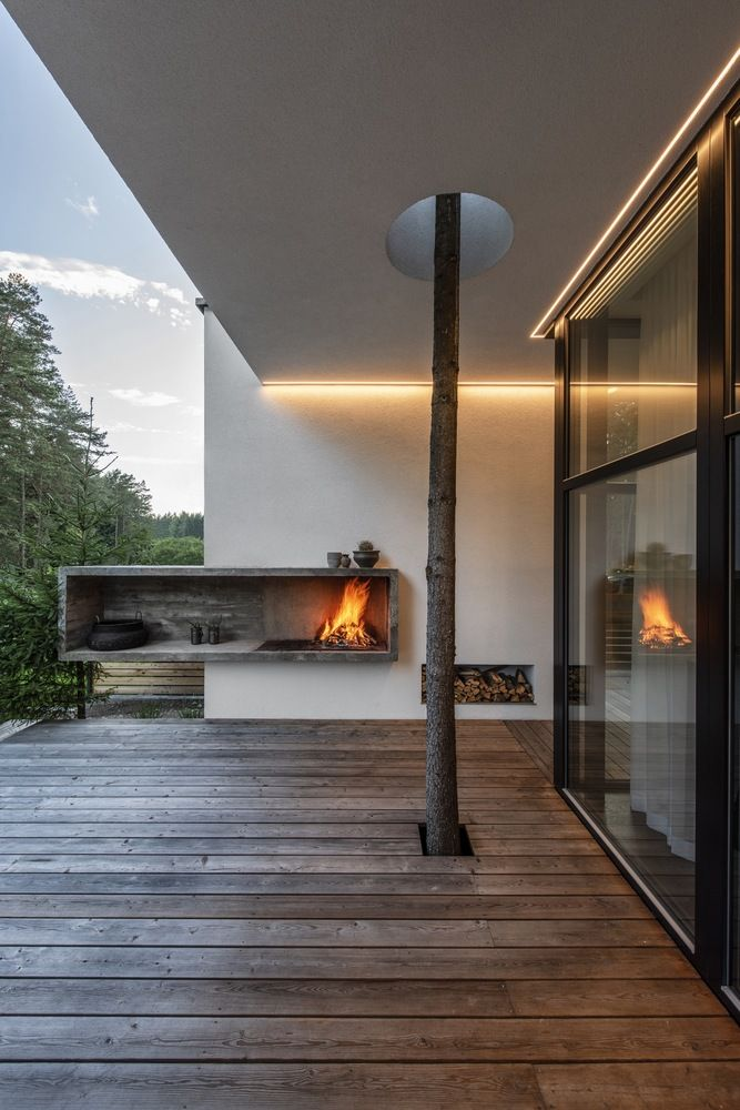 The deck features an open fireplace and a tree growing through the deck for more coziness