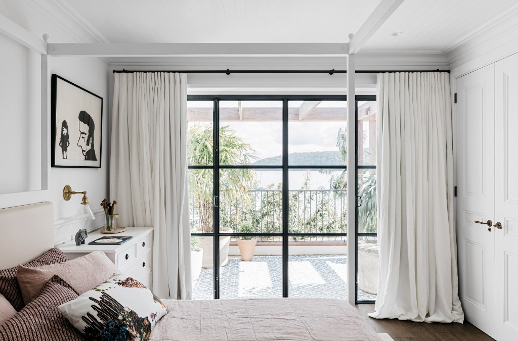 The master bedroom is fully opened to outdoors through a glazed wall with a door