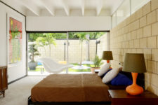 06 The master bedroom is opened up to outdoors with glass doors, there's colorful furniture and an artwork