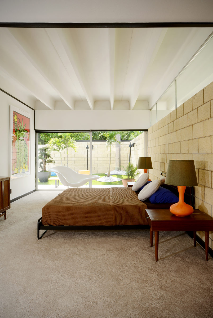 The master bedroom is opened up to outdoors with glass doors, there's colorful furniture and an artwork