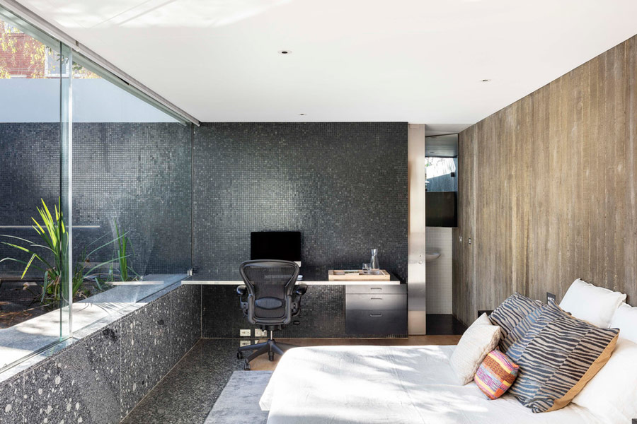 The master bedroom shows off dark stone and tile walls, a weathered wood wall and a comfy bed plus a working space