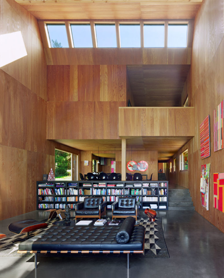 The space divider is a giant bookshelf and the upper floor features more private spaces