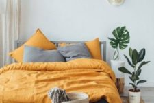 06 a boho bedroom with grey and yellow bedding that creates a contrasts and brings sunlight to the space