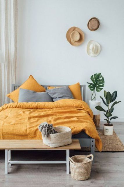 a boho bedroom with grey and yellow bedding that creates a contrasts and brings sunlight to the space