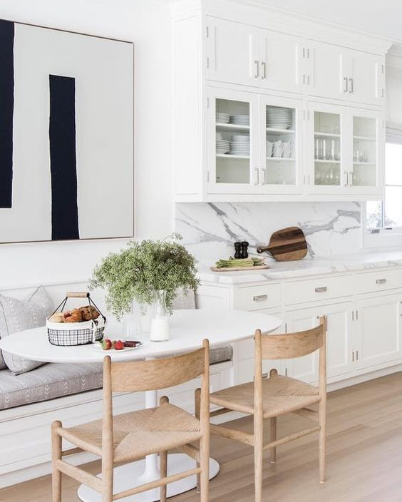 a chic white kitchen with a comfy dining nook, a banquette seating, wooden chairs and an oval table
