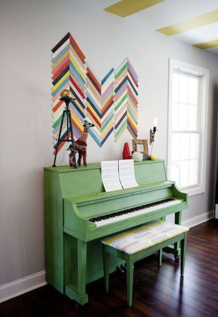 a grass green piano and a bold chevron artwork right on the wall to add color and interest to the space