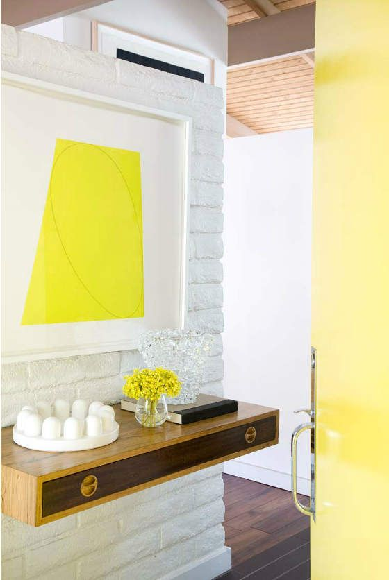 a small floating plywood console with a drawer and a colorful artwork over it for a chic look