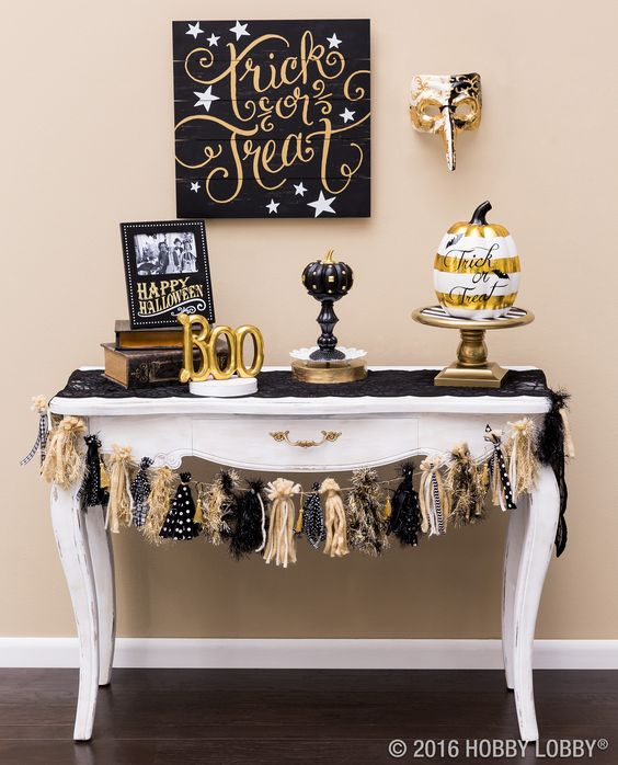 a spooktacular console with fake pumpkins, a tassel garland, a sign and gold letters