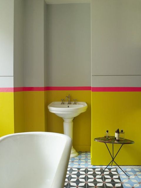 a sunny yellow and light green bathroom with a bold pink stripe looks really bold and unusual
