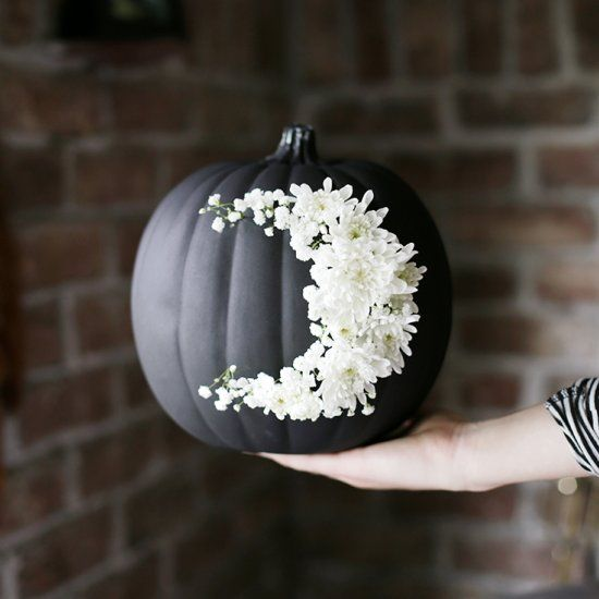 go for creative art decorating your matte black pumpkin with white blooms like that