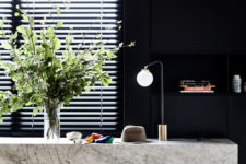 07 The dark entryway shows off a floating stone vanity with lamps and lights